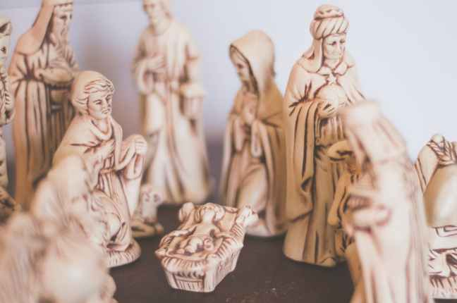 A wood carved nativity scene with the baby Jesus, Mary, Joseph, and the three magi.