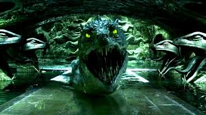 The mouth of a basilisk (giant snake) from Harry Potter flanked by two snake head statues on each side.