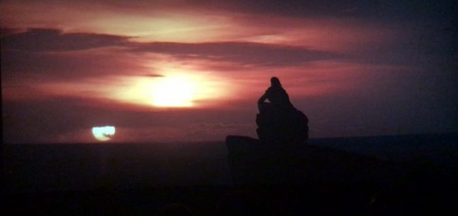 A Shadowed Luke Skywalker looking off at a binary sunset in Star Wars: The Last Jedi.