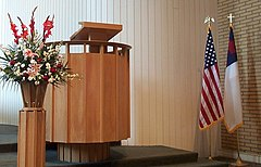 From left to right: flower arrangement, pulpit, U.S. flag, and the Christian flag on flag poles with eagle and cross finials respectively, in Covenant Presbyterian Church, Long Beach, California, United States.
