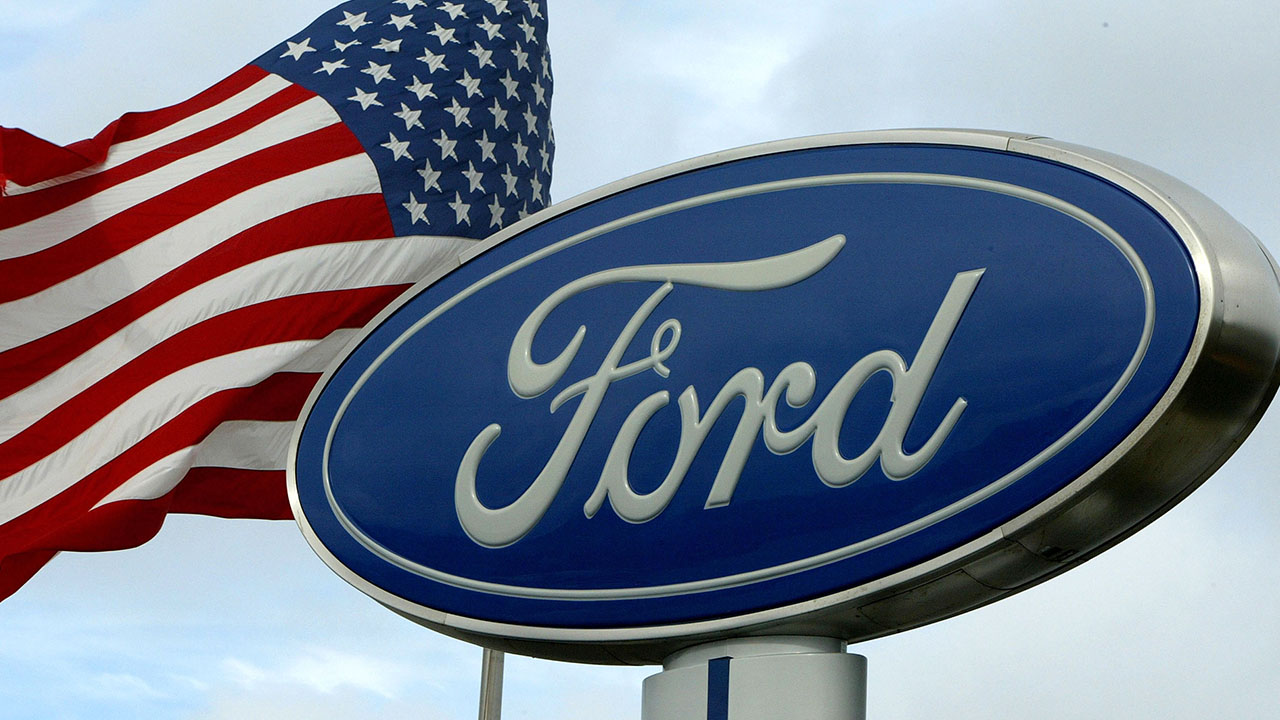 The Ford Motor Company logo next to an American Flag wavering.