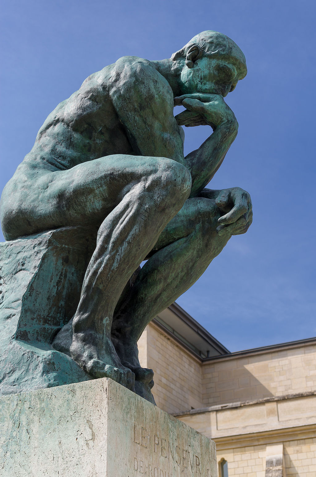 Rodin's the Thinker, a statue of a naked man sitting with his arm under his chin.