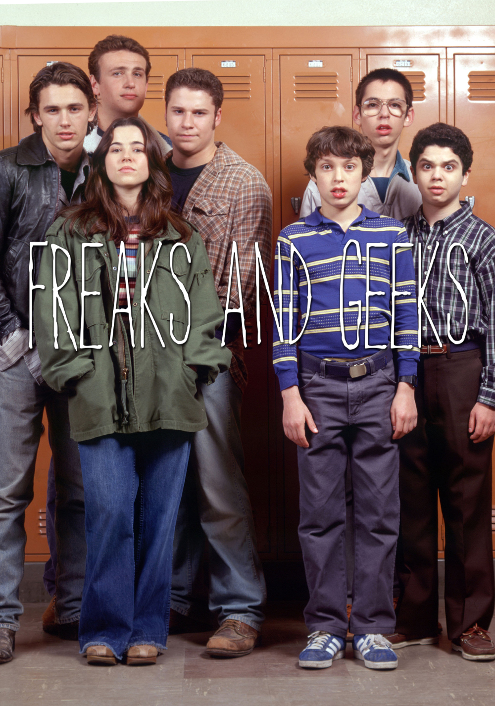"A poster of 7 teenagers in front of lockers. Four on the left are social rejects. Three on the right are dweebs. Across the image it says ""Freaks and Geeks."" Am image from a short-lived 1999 television show."